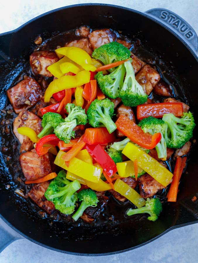 Salmon and stir fry vegetables cooking in a large nonstick skillet.