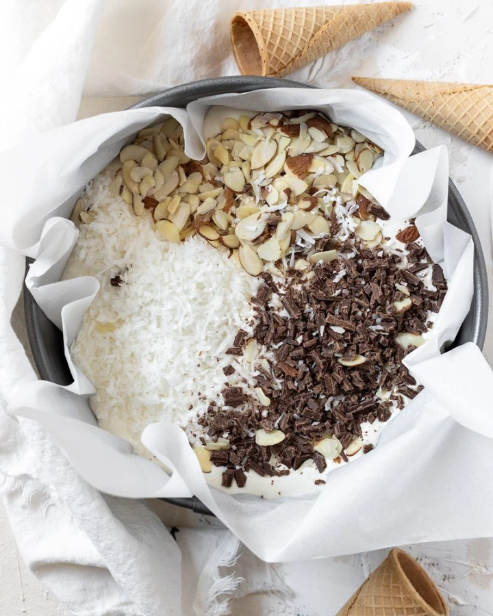 chocolate coconut and almonds in a cake pan on top of the ice cream