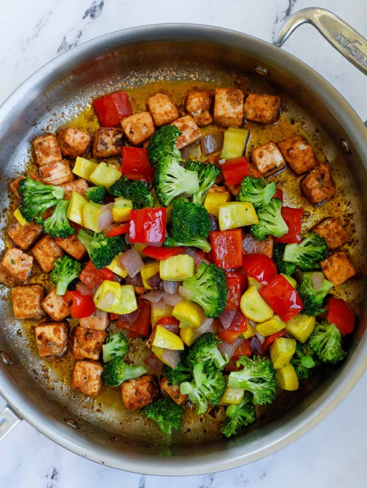 top down shot of salmon with vegetables in a skillet