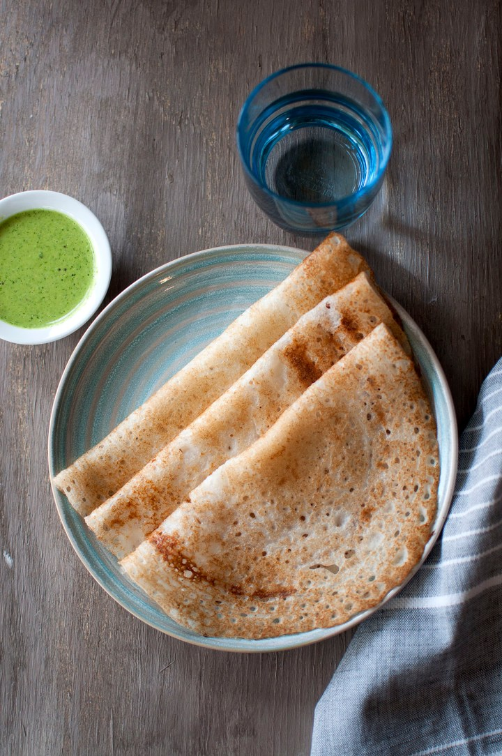 Blue plate with poha dosa and a bowl with green chutney