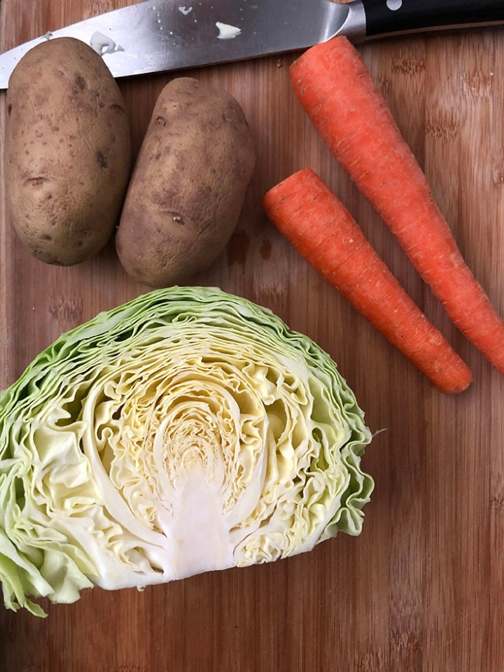 Chopping board with half head of cabbage, 2 carrots and 2 russet potatoes