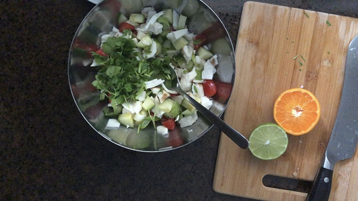 Steel bowl with chopped coconut meat, cucumber, tomatoes, scallions, cilantro and halved lime, orange on the side