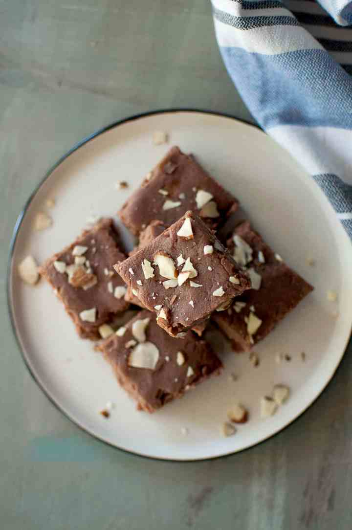 Grey plate with a stack of chocolate burfi squares topped with sliced almonds
