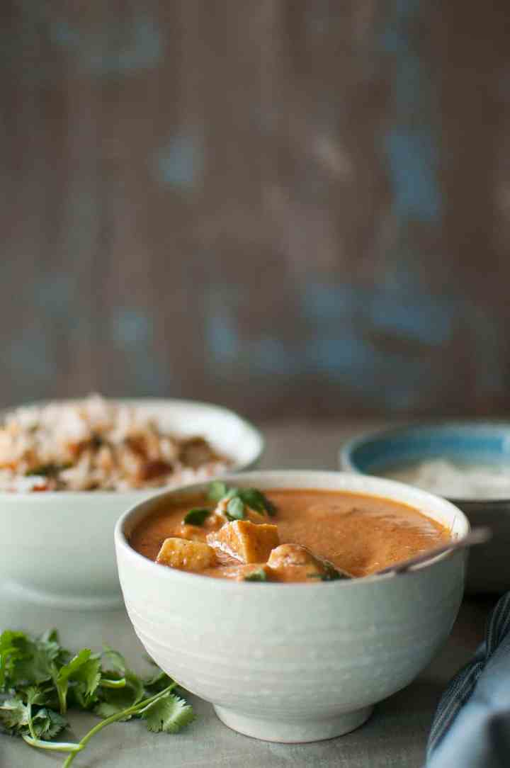 White bowl with paneer curry topped with cilantro
