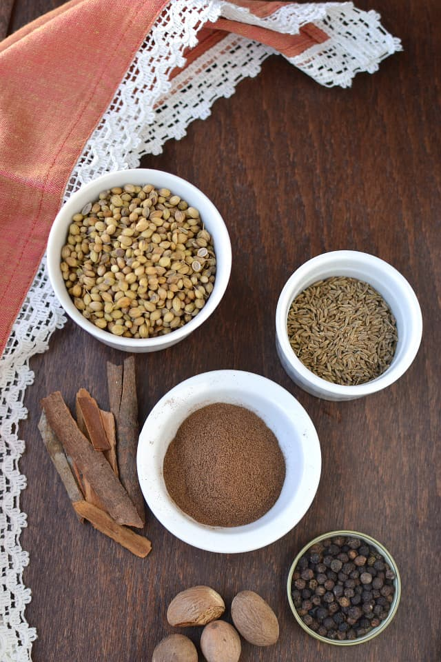Ingredients needed for the recipe - White bowls with whole spices - coriander, cumin, allspice, peppercorn, cinnamon and nutmeg