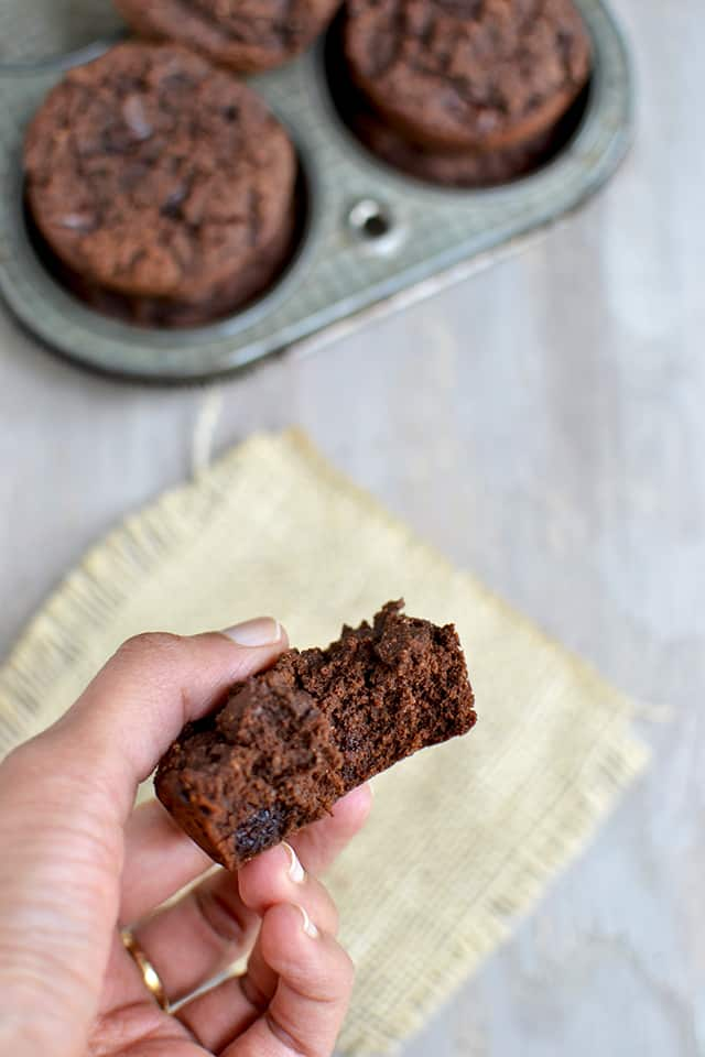 Fingers holding bitten chocolate muffin