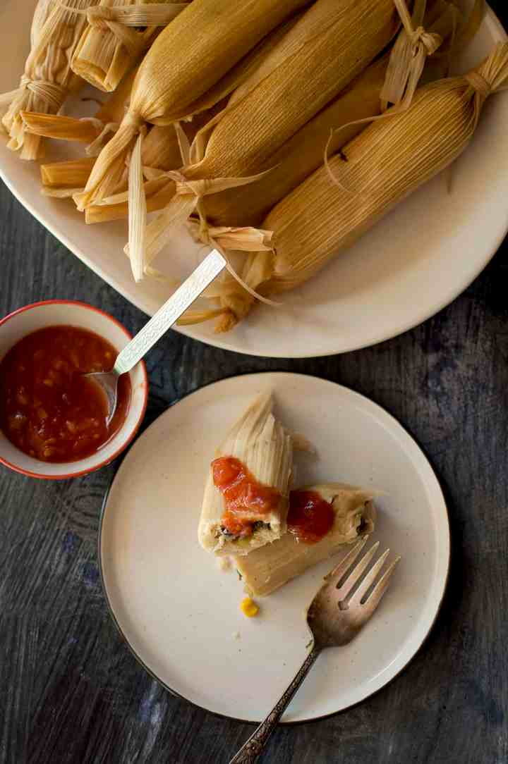 White plate with tamale topped with salsa