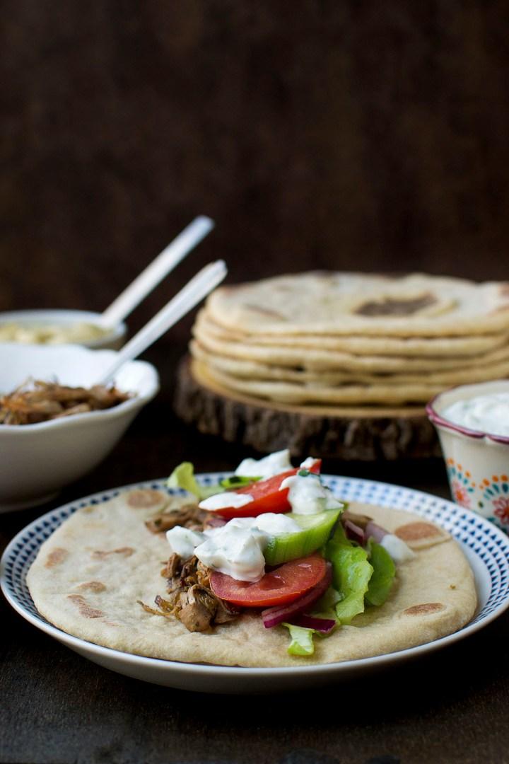 White plate with pita topped with jackfruit stuffing, veggies and yogurt
