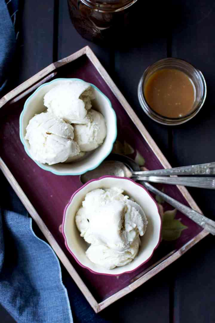 Painted bowls with scoops of sweet milk ice cream served on a tray with caramel sauce on the side