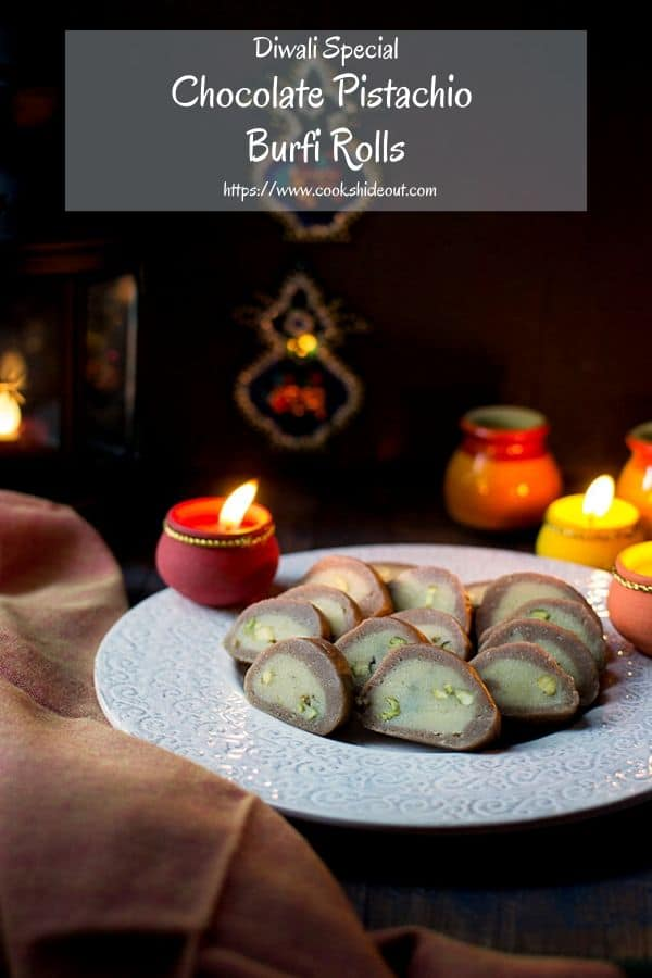 Plate of pista burfi with lit lamps for Diwali