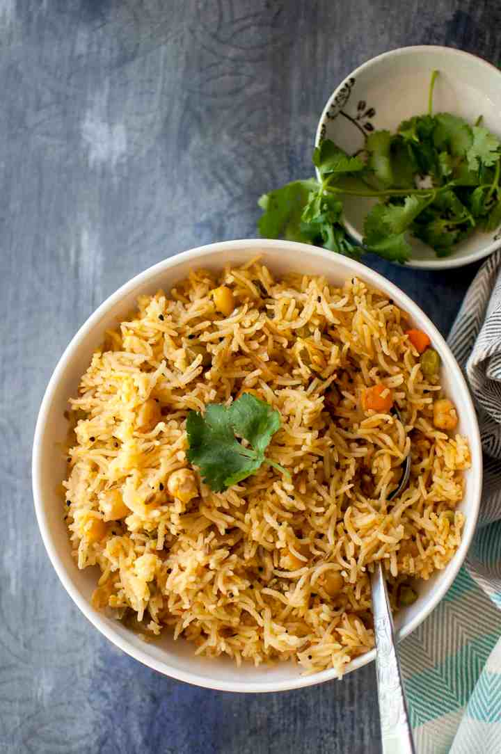 White bowl with Achari vegetable Pulao with a cilantro sprig on top
