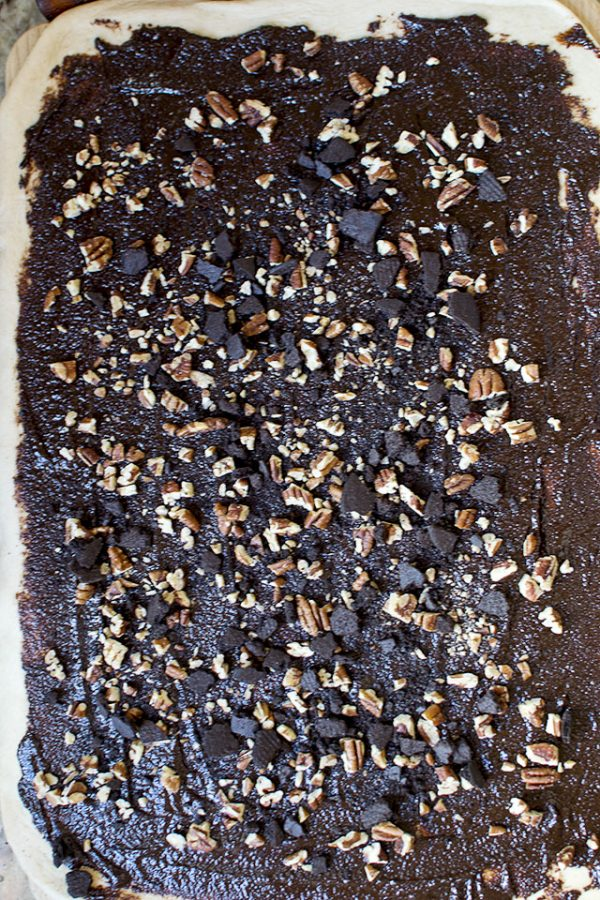 Spread the chocolate filling over the dough all the way to the edges. Sprinkle in the chopped nuts and crushed chocolate cookies.