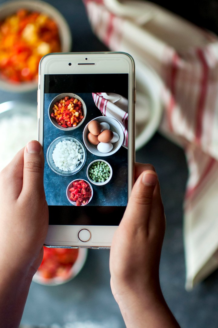 Hand holding a phone with a photo of onions, bell peppers, tomatoes, green peas and eggs