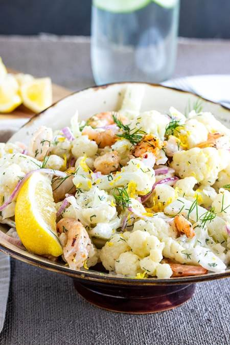 cauliflower salad with shrimp and onions in a big bowl with lemon zest on top