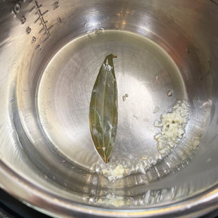 bay leaf and garlic being sautéed in oil