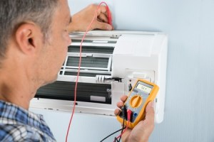 Engineer doing an electrical test on air con unit
