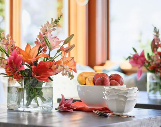 Home kitchen table setting with fruit and flowers.