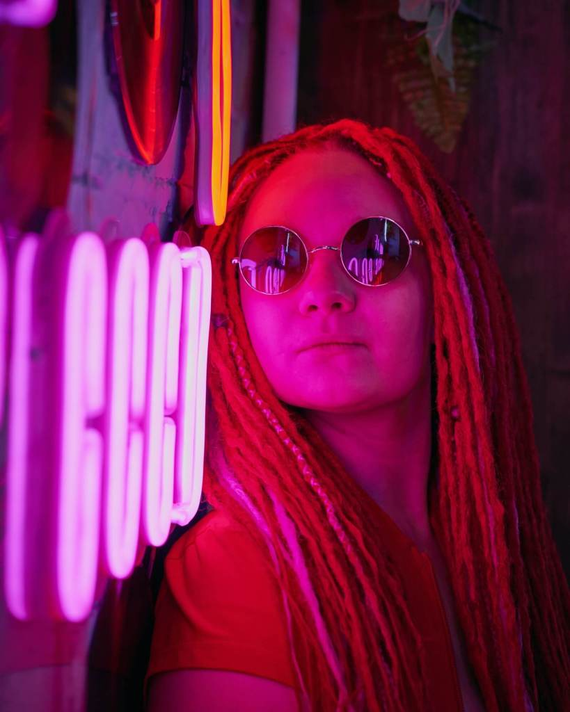 Girl in neon lights, beautiful woman in sunglasses, with pink hair, with dreadlocks pigtails