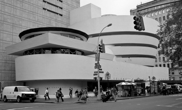 A black and white photo of the Guggenheim Museum in NYC. Traffic lights and pedestrians on the sidewalk are in the foreground. The museum's famous architecture looks like lots of big smooth white shapes stacked on each other: A big rectangle at the bottom, four big circles stacked on the right, and a second rotunda with windows on the left.