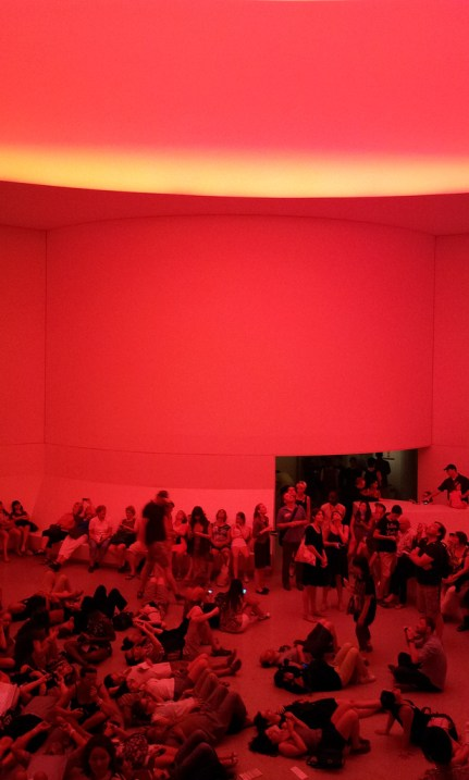 The Guggenheim's large round lobby, shown completely bathed in ruby-red light. The benches and floor area are crowded with people reclining, laying on the floor, and looking upwards at the light source.