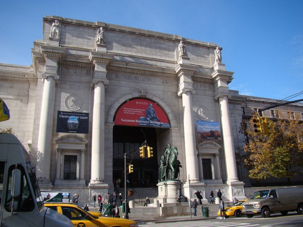 The entrance to the American Museum of Natural History. Clear blue sky, pedestrians walking up the stairs, banners hanging on the facade, and taxicabs in the foreground. Architecture is stately, four tall columns and ornate inscriptions and statues near the roofline.