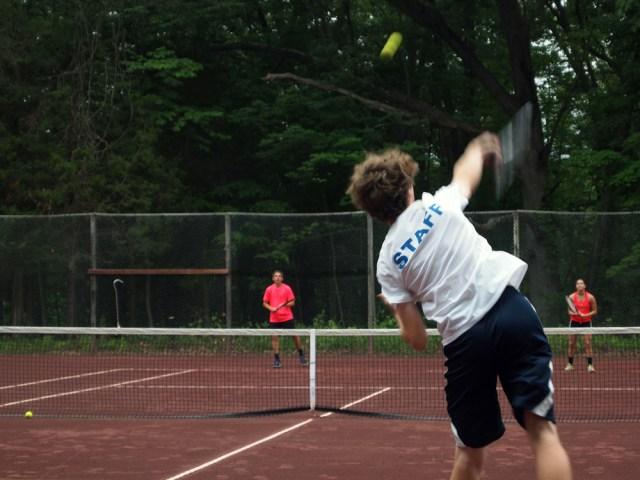 A high school player serves at the Filipek tennis tournament at