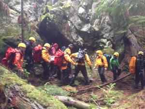 SAR members carrying the stretcher in the rain