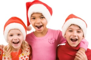 Photo of happy friends in Santa caps laughing over white background