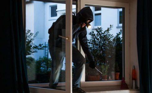 olycom - acquarone - Burglar breaks into an apartment. Symbol image.