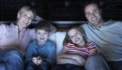 Family Watching TV At Night Sitting On Sofa Together