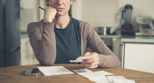 A young woman is sitting in her kitchen and is loking at her receipts at home while using a smart phone