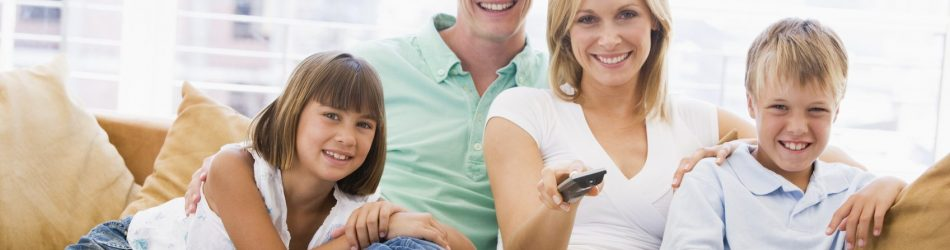 Family sitting in living room with remote control smiling