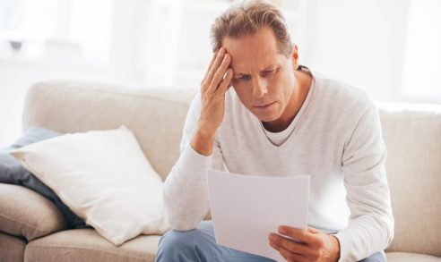 Depressed mature man holding paper and watching it while sitting on the couch at home