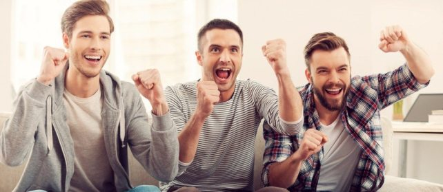 Three happy young men watching football game and keeping arms raised while sitting on sofa