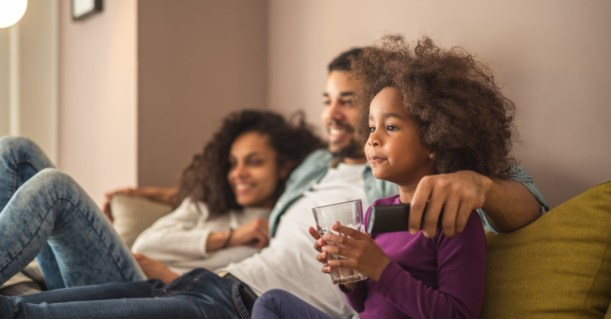 family with little girl sitting on couch watching tv