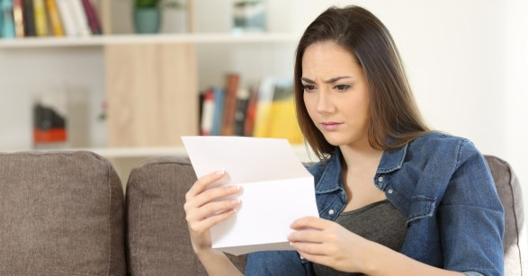 woman holding bill looking confused