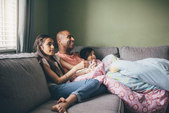 dad and daughters watching tv