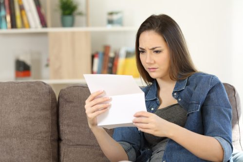 Worried woman reading paper