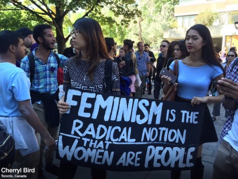 "Students carry a sign that reads ""FEMINISM is the radical notion that WOMEN are PEOPLE."" Photo by Cherryl Bird"