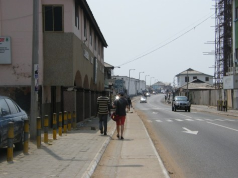 Two people walking on the sidewalk