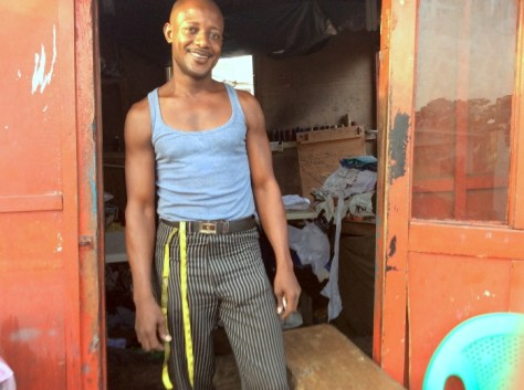 Annam Sowah, the tailor, stands in the doorway of his shop