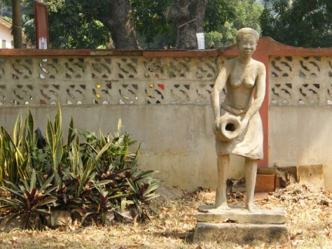 A sculpture of a female figure pouring water from a ceramic jug
