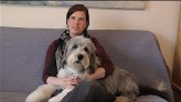 Elena Kaufman sits on a couch with her hands wrapped around her dog, who sits across her lap