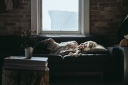 A woman on a couch under a window