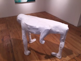 A white table covered in leather, with a protruding human head and feet