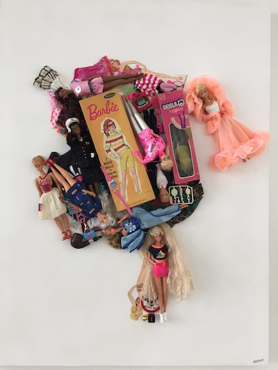 Barbie dolls and other objects glued to a board