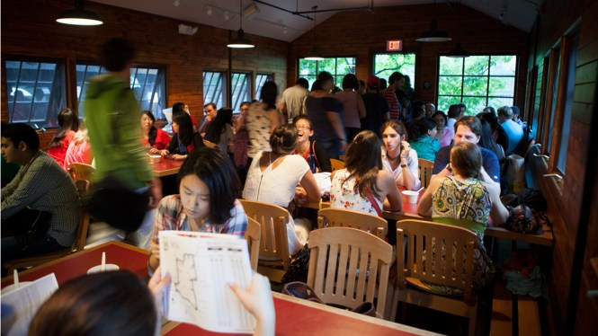 Lots Of Students Sitting At Tables In The Red Barn Cornell S Graduate Student Center