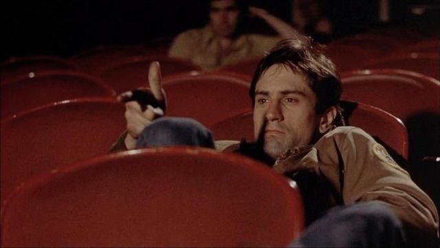 Travis richt in de bioscoop zijn hand als een pistool op het scherm