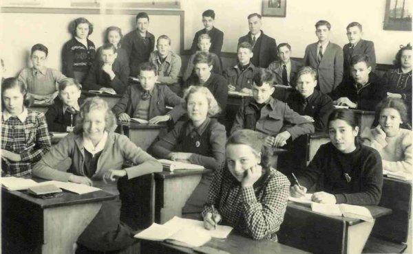 In de derde rij, net 'terug' uit Indië in de HBS van 1946-1947, met hemd, overhemd, trui en colbert. Zijn zus Loes zit rechts vooraan met donkere trui.