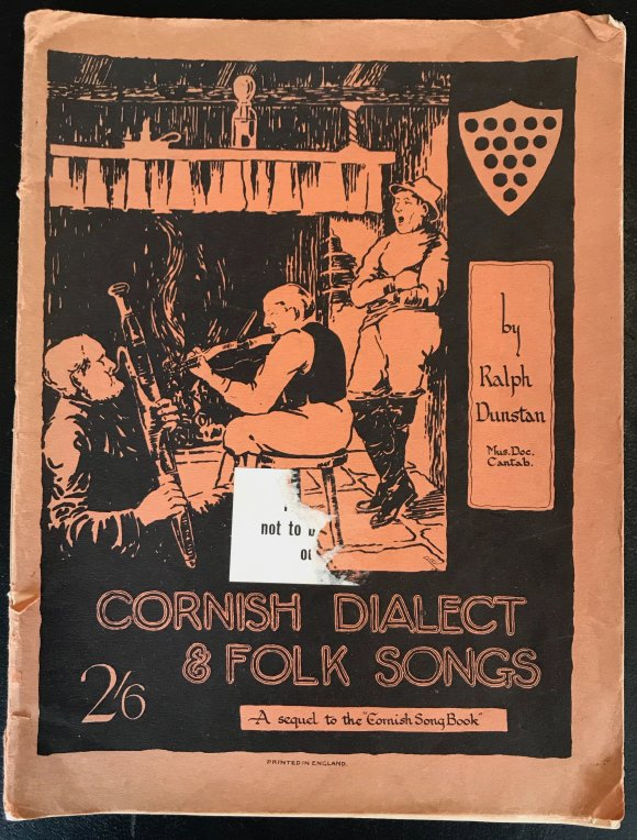 Cover of Ralph Dunstan's Cornish Dialect and Folk Songs book, 1932 showing an illustration of a bassoon player, fiddler and a man in long boots leaning against the wall, in front of a roaring open fire.
